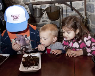 4-17-10   Earth Day at Perfect Christmas Tree Farm       (l-r) Bobby Saccaro, 5, from Phillipsburg; Joey Palumbo, 2, from Phillipsburg; and Mia Latif, 4, from Stewartsville, get a close up view of earthworms through a magnifying glass. Carmen Pirotte, from Stewarstville, was on hand to teach all about worms.        photo by Cathy Miller