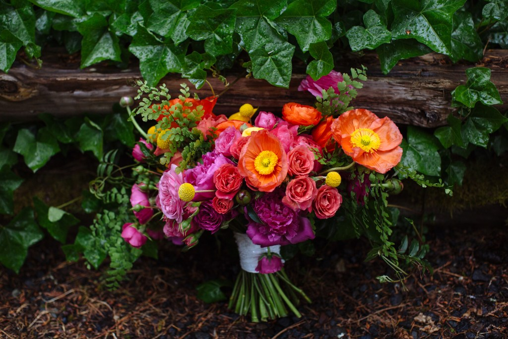 Kiana Lodge Wedding on Bainbridge Island, WA | Vibrantly colored, loosely arranged bridal bouquet with pink, orange, and yellow blooms | Perfectly Posh Events, Seattle Wedding Planning | Shane Macomber Photography | Floral Design by Flora Nova