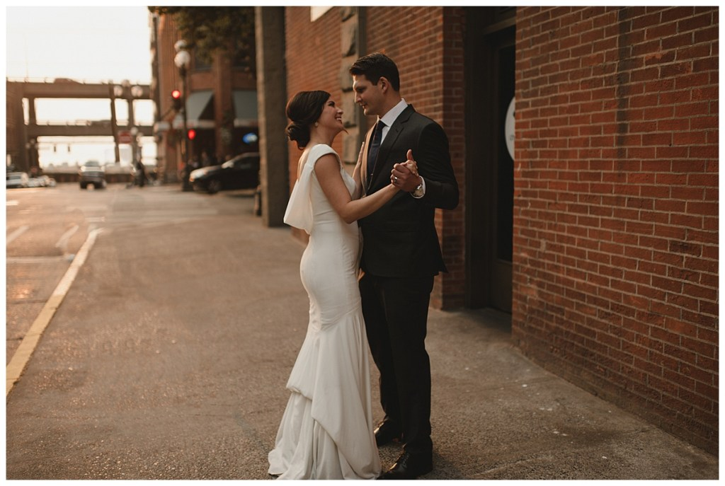 Bride and groom dance outside on the sidewalks of Seattle