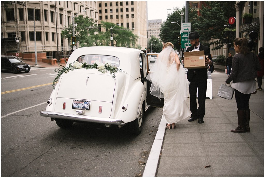 Bride steps in white vintage car decorated with white flowers and greenery, Axis Pioneer Square wedding, Seattle wedding, Perfectly Posh Events, Seattle Wedding Planner, Photo by Roland Hale