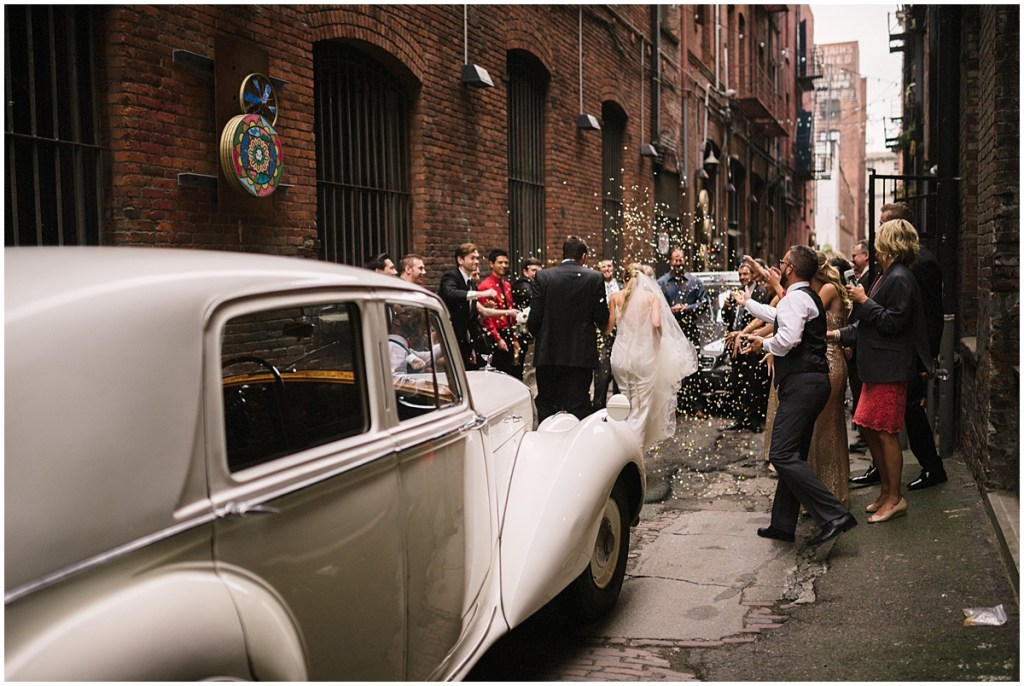 Guests celebrate newlywed bride and groom with white classic car in foreground, Axis Pioneer Square wedding, Seattle wedding, Perfectly Posh Events, Seattle Wedding Planner, Photo by Roland Hale