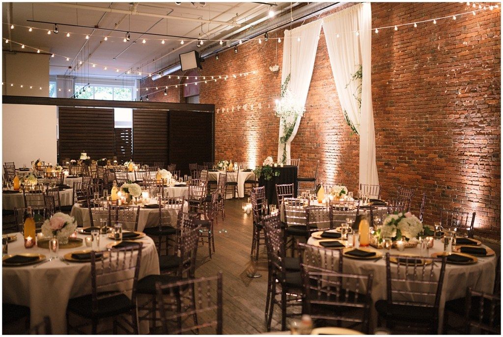 Wedding dinner tables set up with white table cloths and floral centerpieces in front of rustic brick wall, Axis Pioneer Square wedding, Seattle wedding, Perfectly Posh Events, Seattle Wedding Planner, Photo by Roland Hale