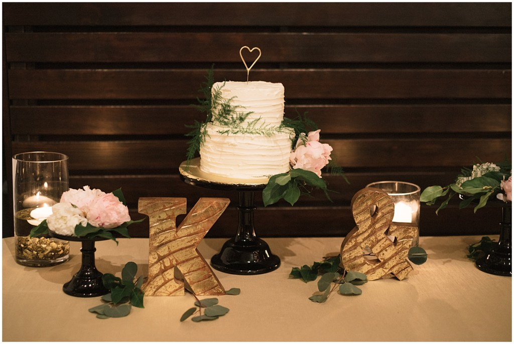 Two tier wedding cake on dessert display table with couple