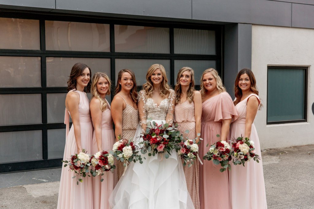 Bride and bridesmaid in blush colored gowns pose outside while holding ivory and burgundy floral bouquets, Fremont Foundry wedding, Seattle wedding, wedding planning and design by Perfectly Posh Events, Seattle Wedding Planner, Photo by Brittney Hyatt
