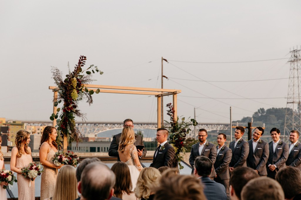 Bride and groom exchange their vows in front of guests on rooftop with view of Seattle