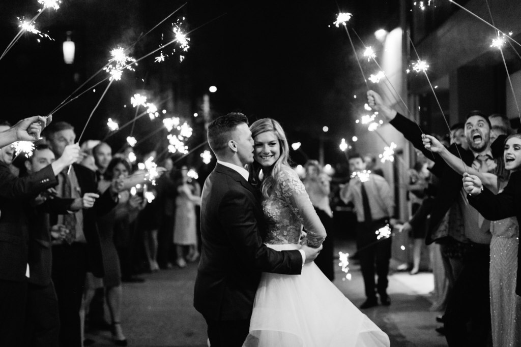 Bride and groom are sent off by guests with festive sparklers, black and white photo, Fremont Foundry wedding, Seattle wedding, wedding planning and design by Perfectly Posh Events, Seattle Wedding Planner, Photo by Brittney Hyatt