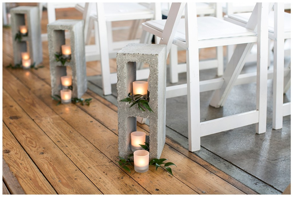 Metropolist Wedding in Seattle, WA | Industrial modern wedding design, using cinder blocks down the aisle and at the altar with greenery and candles tucked in and around | Seattle Wedding Planner, Perfectly Posh Events | Katie Parra Photography | Floral Design by Sublime Stems
