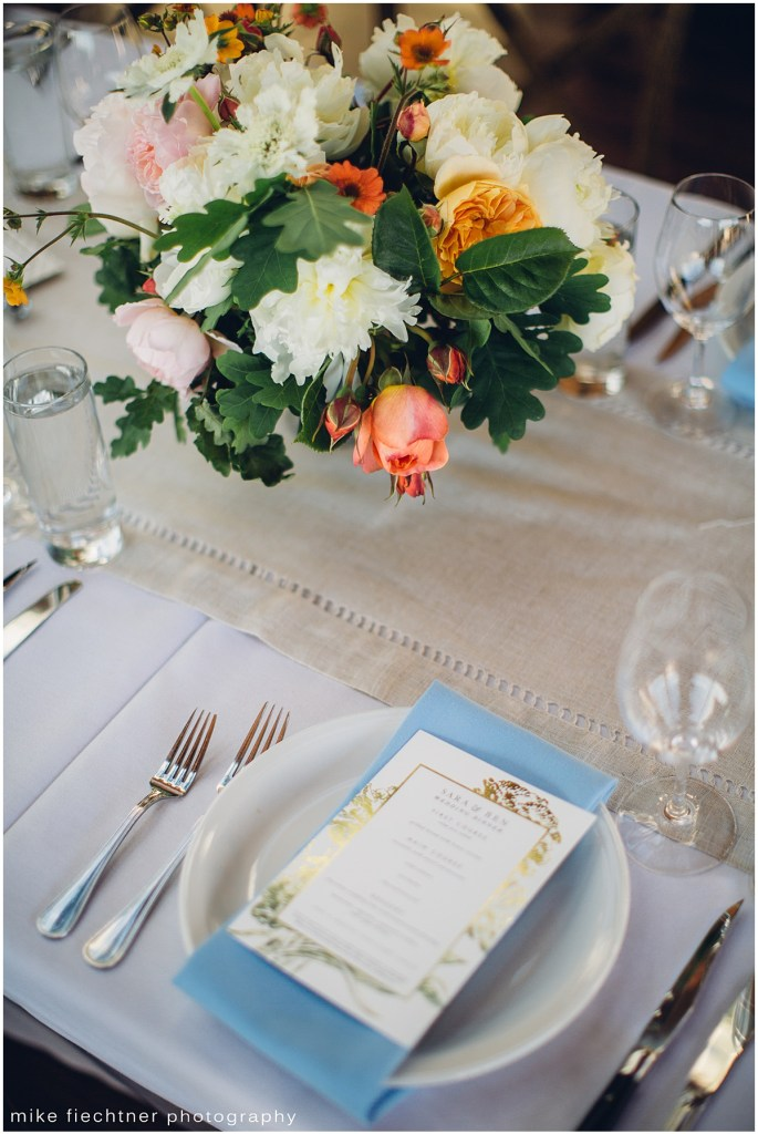 Wedding table setting with white tablecloth, linen table runner, blue napkins, and a white and coral floral centerpiece, Olympic Rooftop wedding, Seattle wedding, wedding planning by Perfectly Posh Events, Seattle and Portland Wedding Planner, Photo by Mike Fiechtner Photography
