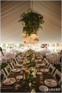 Long rustic wood table set up for wedding reception with floral centerpieces and dramatic vintage chandeliers hanging overhead, The Lodge at Fall City wedding, Seattle wedding, planning and design by Perfectly Posh Events, Seattle Wedding Planner, Photo by Max & Sam Photography