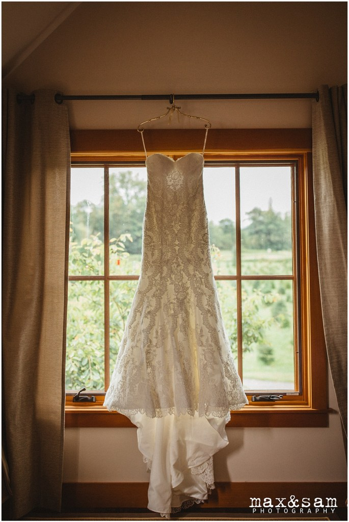 Strapless, lace mermaid wedding gown hanging in front of window, The Lodge at Fall City wedding, Seattle wedding, planning and design by Perfectly Posh Events, Seattle Wedding Planner, Photo by Max & Sam Photography
