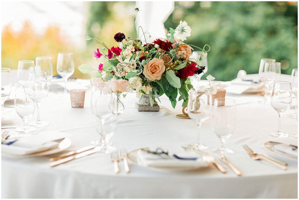 Wedding reception dinner table covered in white table cloth and decorated with with a blush, peach, and burgundy floral centerpiece, Admiral