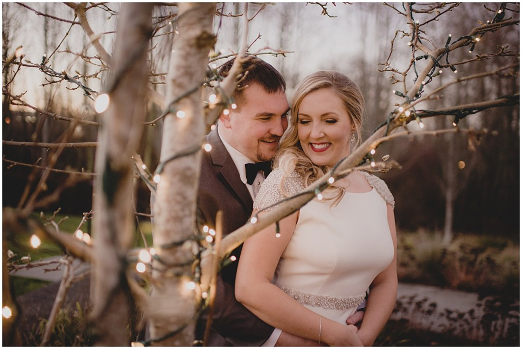 A groom embraces his bride while posing outside next to a tree decorated in white holiday lights, New Years Eve wedding, Cedarbrook Lodge wedding, Seattle wedding, Perfectly Posh Events wedding planning, Washington wedding planner, Photo by Carly Bish