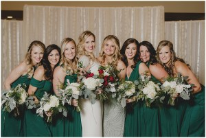 Bride poses indoors with bridesmaids wearing emerald green gowns, New Years Eve wedding, Cedarbrook Lodge wedding, Seattle wedding, Perfectly Posh Events wedding planning, Washington wedding planner, Photo by Carly Bish