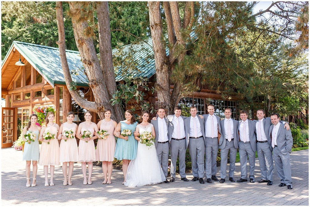 Bride and groom pose outside with their bridesmaids and groomsmen in front of rustic lodge, Kiana Lodge wedding, Perfectly Posh Events wedding planning, Seattle wedding planning, Photo by Amy Soper Photography