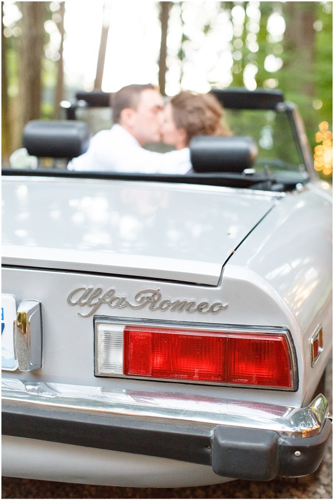 Newlywed bride and groom share a kiss in a silver vintage Alfa Romeo, Kiana Lodge wedding, Perfectly Posh Events wedding planning, Seattle wedding planning, Photo by Amy Soper Photography
