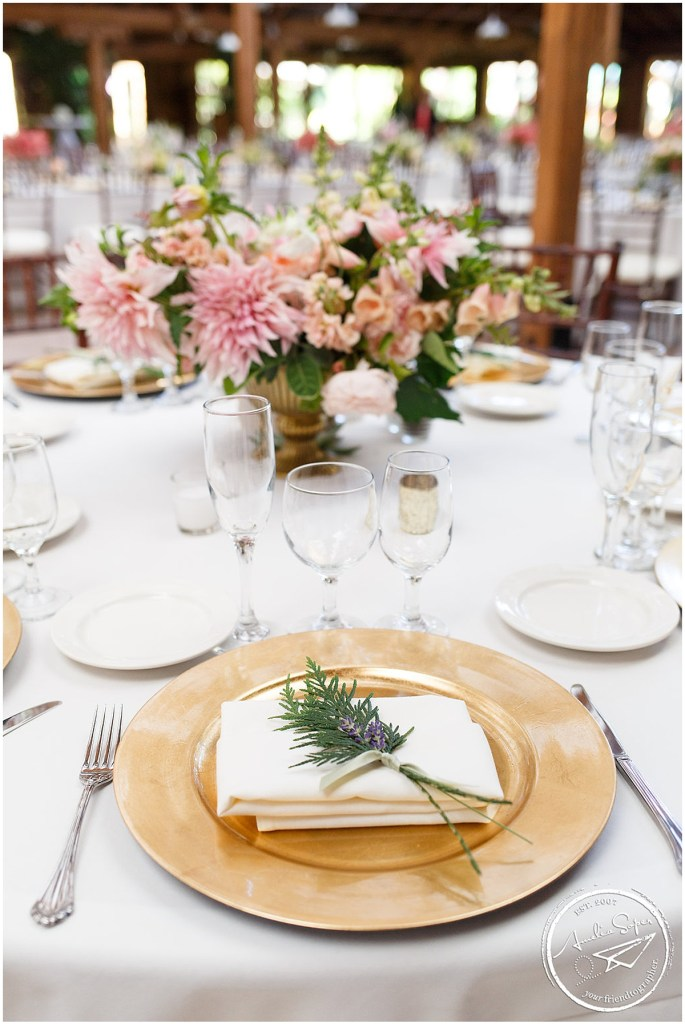 Wedding dinner place setting with a gold charger plate and a sprig of lavender and spruce with a pink floral centerpiece, Kiana Lodge wedding, Perfectly Posh Events wedding planning, Seattle wedding planning, Photo by Amy Soper Photography