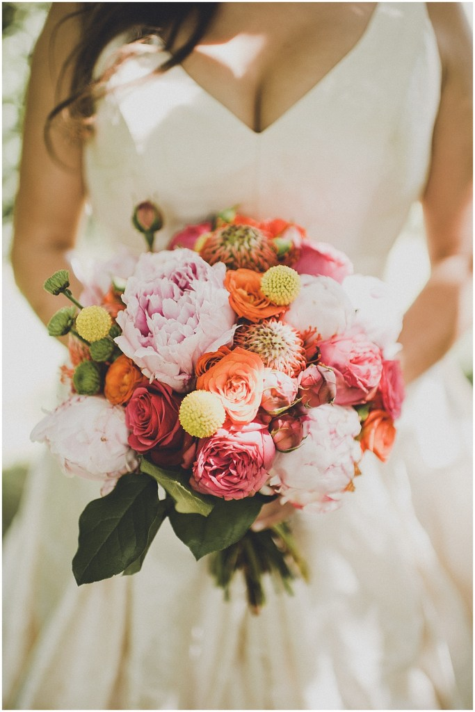 Bride holding a bouquet with pink, coral, blush, and ivory colored flowers, mid century modern wedding, The Foundry by Herban Feast wedding, Seattle wedding, Perfectly Posh Events wedding planning and coordination, Photo by Carina Skrobecki