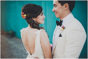 A bride and groom embrace while posing outside in front of teal blue wall, mid century modern wedding, The Foundry by Herban Feast wedding, Seattle wedding, Perfectly Posh Events wedding planning and coordination, Photo by Carina Skrobecki