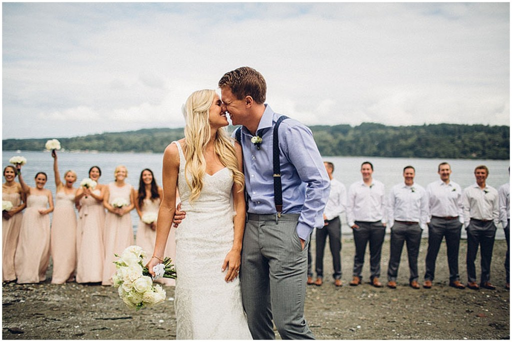 A bride and groom share a kiss as their bridesmaids and groomsmen cheer them on, Washington wedding, Perfectly Posh Events wedding planning, Washington wedding planner, Photo by Mike Fiechtner Photography