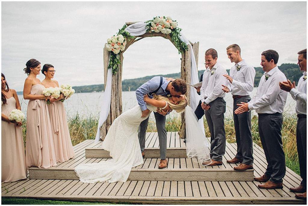 Groom dips his bride as he kisses her after exchanging vows at their outdoor waterfront wedding ceremony, Washington wedding, Perfectly Posh Events wedding planning, Washington wedding planner, Photo by Mike Fiechtner Photography