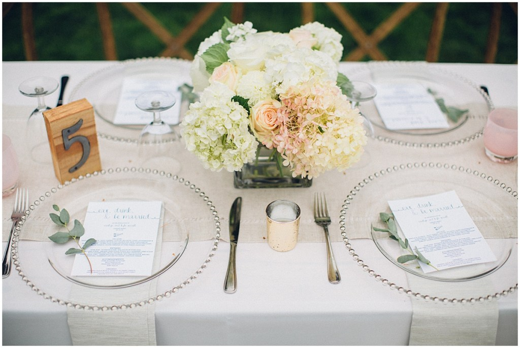 Close up of wedding dinner table decorated with ivory and blush floral centerpieces, a white table cloth, and pink Glassybaby candle jars, Washington wedding, Perfectly Posh Events wedding planning, Seattle Wedding Coordinator, Photo by Mike Fiechtner Photography