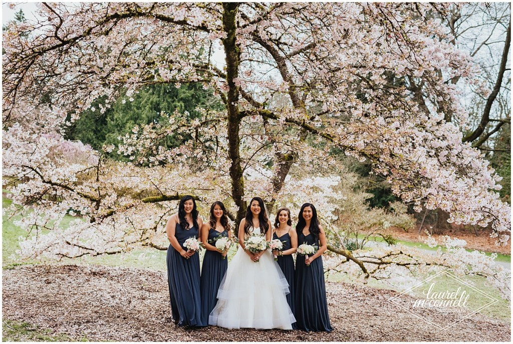 Bride poses with her bridesmaids in navy gowns while holding ivory and blush floral bouquets while standing under a blooming cherry tree, The Foundry by Herban Feast wedding, Seattle wedding, wedding planning by Perfectly Posh Events, Photo by Laurel McConnell Photography