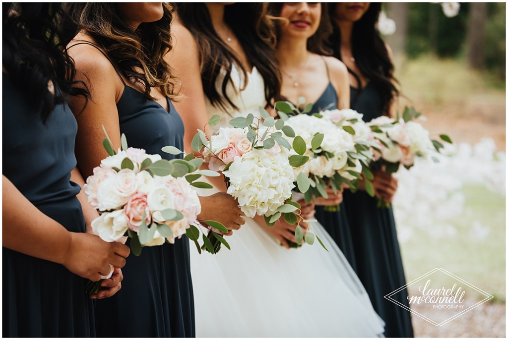 Close up of bride posing with her bridesmaids in navy gowns while holding ivory and blush floral bouquets, The Foundry by Herban Feast wedding, Seattle wedding, wedding planning by Perfectly Posh Events, Photo by Laurel McConnell Photography