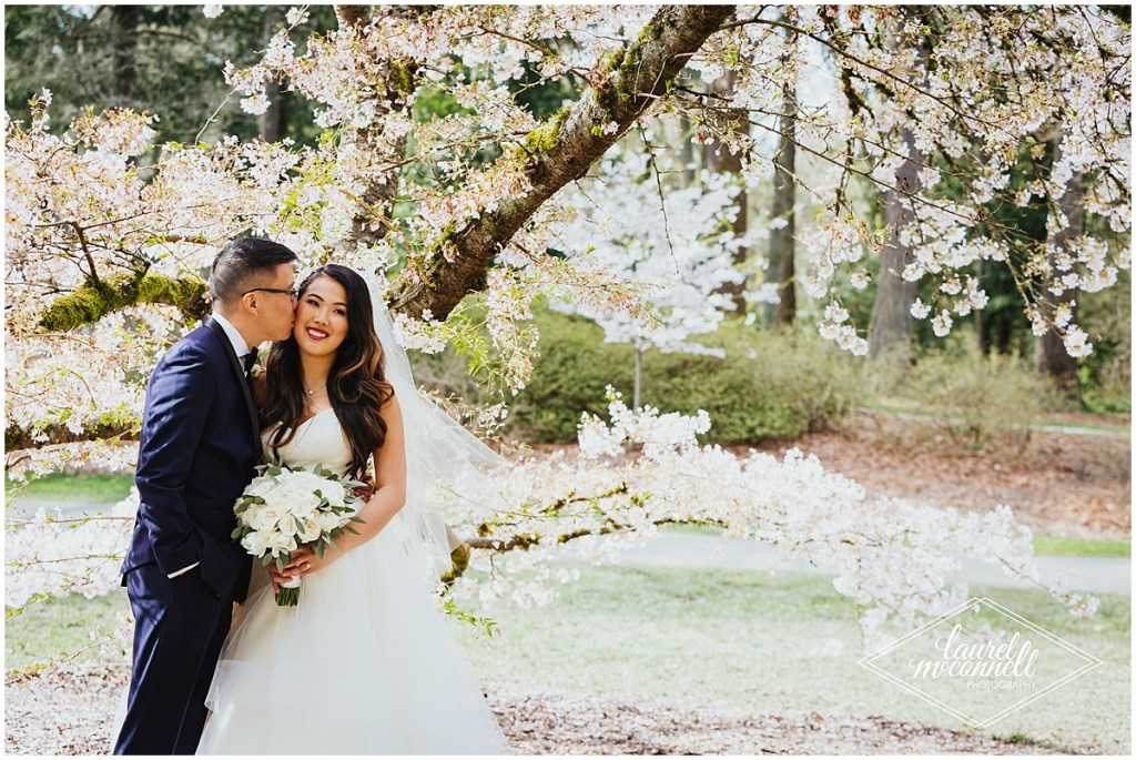 A groom gives his bride a kiss while they stand under a cherry tree covered in blossoms, The Foundry by Herban Feast wedding, Seattle wedding, wedding planning by Perfectly Posh Events, Photo by Laurel McConnell Photography