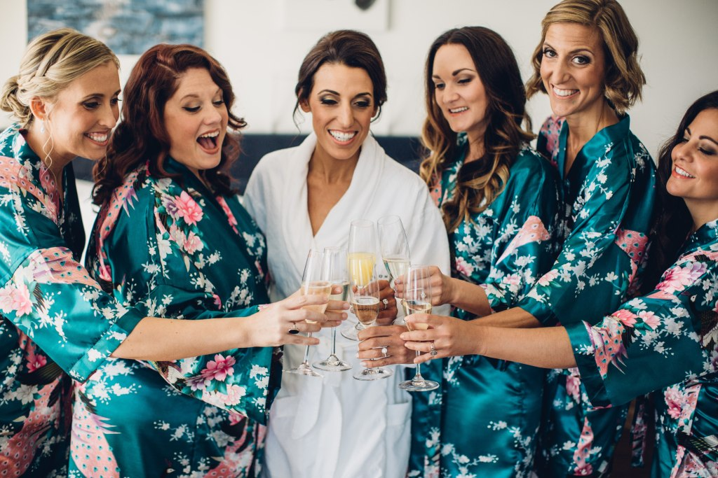 Before her wedding a bride in a white robe shares a champagne toast with her bridesmaids in blue floral print robes, Italian inspired wedding, Bell Harbor at Pier 66 wedding, Seattle wedding, planning by Perfectly Posh Events, Seattle wedding planner, Photo by Mike Fiechtner Photography
