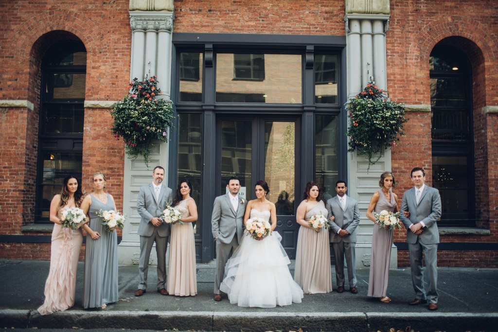 A bride and grown pose with their bridesmaids and groomsmen in front of a old brick building in downtown Seattle, Italian inspired wedding, Bell Harbor at Pier 66 wedding, Seattle wedding, planning by Perfectly Posh Events, Seattle wedding planner, Photo by Mike Fiechtner Photography