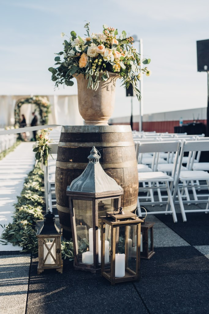 A urn filled with large greenery and coral flower bouquets sit on top of a wine barrel and surrounded by iron lanterns with pillar candles at a rooftop wedding ceremony, Italian inspired wedding, Bell Harbor at Pier 66 wedding, Seattle wedding, planning by Perfectly Posh Events, Seattle wedding planner, Photo by Mike Fiechtner Photography