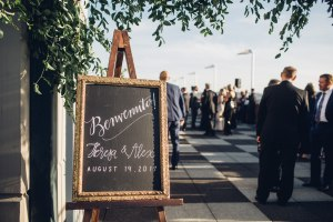 Hand drawn sign on a chalkboard welcomes guests to wedding ceremony in Italian, Italian inspired wedding, Bell Harbor at Pier 66 wedding, Seattle wedding, planning by Perfectly Posh Events, Seattle wedding planner, Photo by Mike Fiechtner Photography