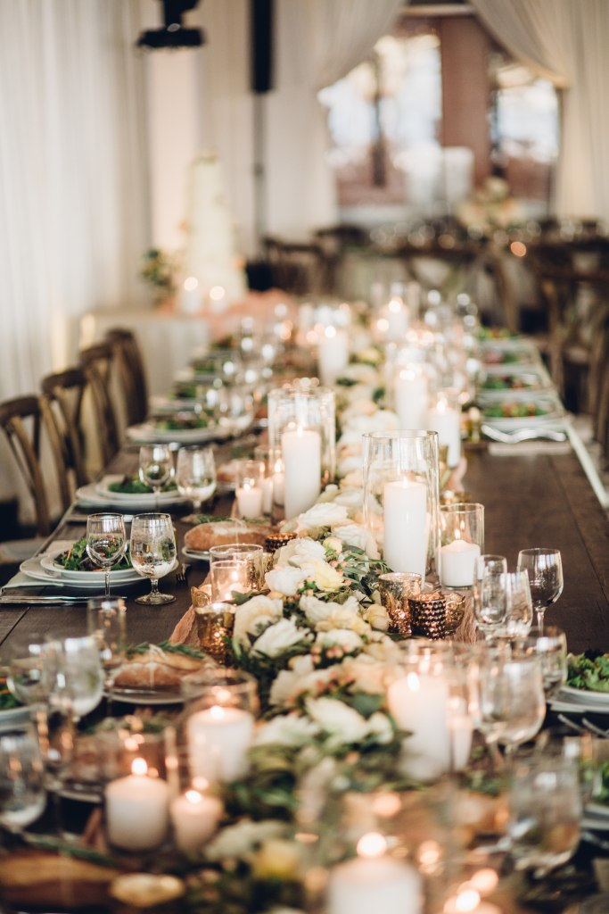 A long dinner table at a wedding reception is set up with floral centerpieces and white pillar candles, Italian inspired wedding, Bell Harbor at Pier 66 wedding, Seattle wedding, planning by Perfectly Posh Events, Seattle wedding planner, Photo by Mike Fiechtner Photography