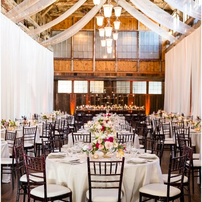 Round wedding reception dinner tables covered in white tables cloths and ivory, blush, and red floral centerpieces in a rustic wood indoor room covered in white drapes, Sodo Park wedding, Seattle wedding planner, Perfectly Posh Events, Photo by La Vie Photography