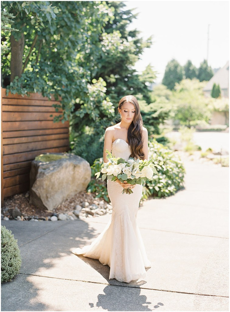 Bride poses outside in a beaded mermaid gown while holding a large bouquet with ivory florals and greenery, DeLille Cellars wedding, Woodinville wedding, Perfectly Posh Events wedding coordination, Photo by Great Romance Photography