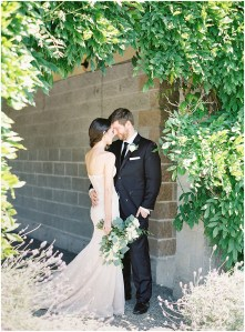 Bride and groom pose under entryway covered in vines, DeLille Cellars wedding, Woodinville wedding, Perfectly Posh Events wedding coordination, Photo by Great Romance Photography