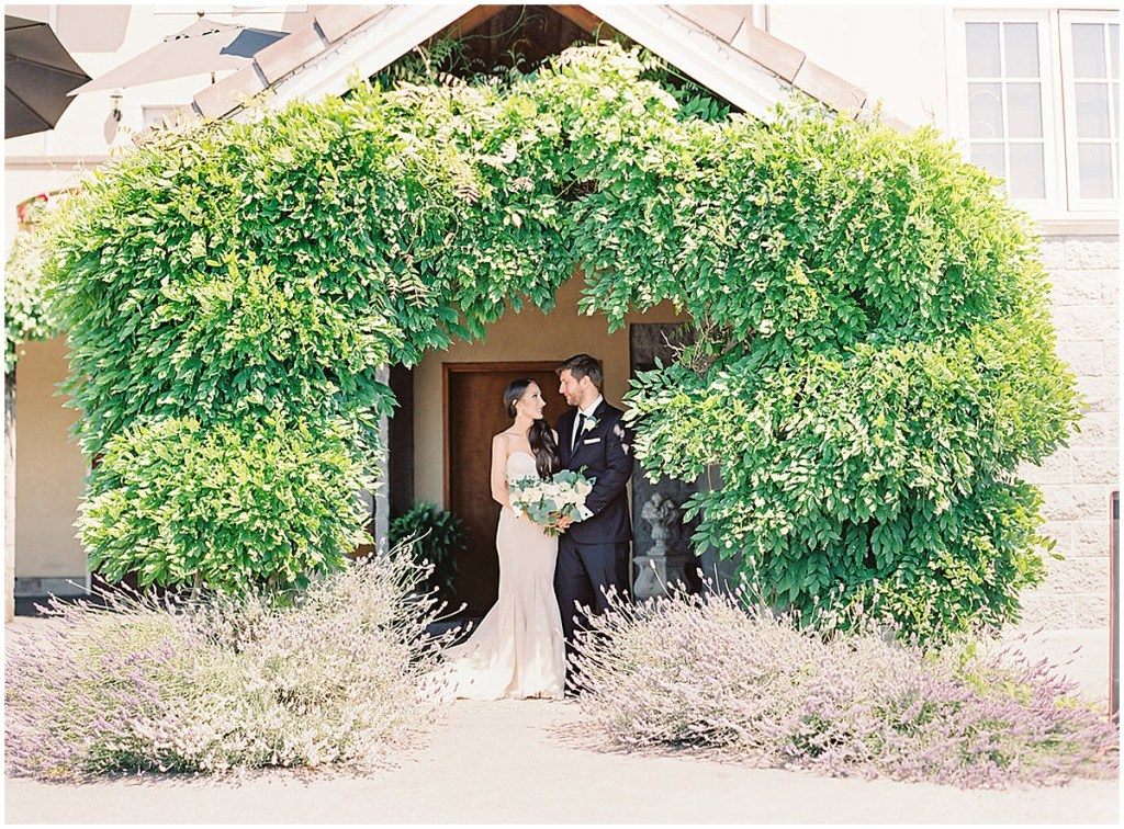 Bride and groom smile at each other while standing under an archway covered in vines and two lavender bushes, DeLille Cellars wedding, Woodinville wedding, Perfectly Posh Events wedding coordination, Photo by Great Romance Photography