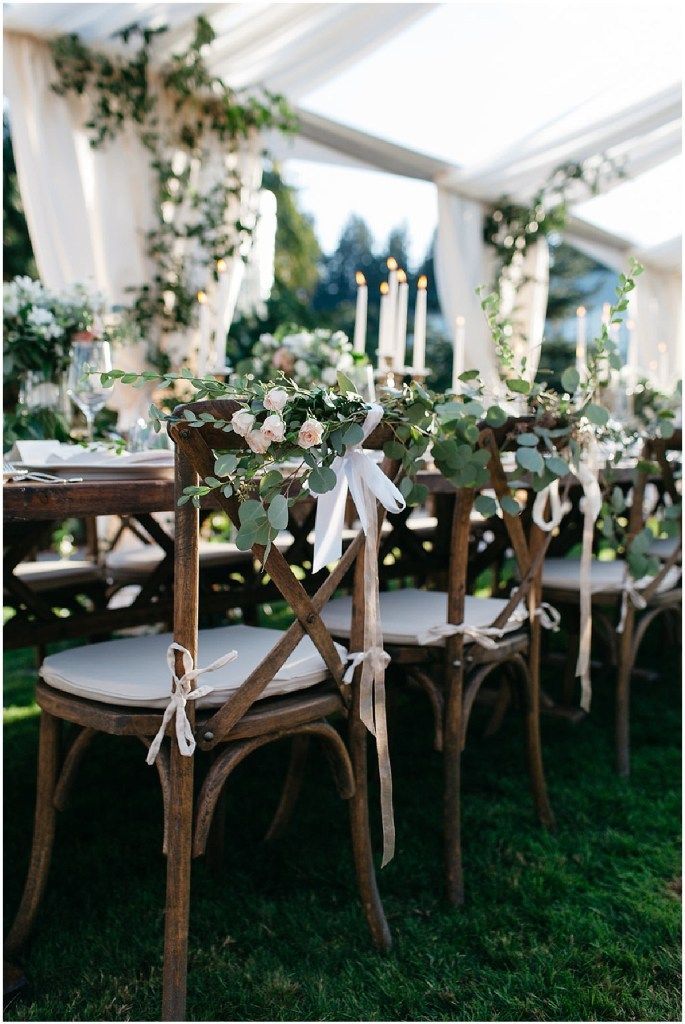 Rustic wood table and dinner chairs set up at a wedding reception decorated with greenery and pink flowers, PNW outdoor summer wedding, Washington wedding designer, Perfectly Posh Events, Photo by Kate Price Photography