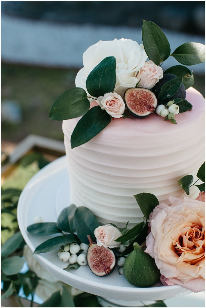 Wedding cake featuring pink and white ombre frosting decorated with pink and ivory flowers, greenery, and figs, PNW outdoor summer wedding, Washington wedding designer, Perfectly Posh Events, Photo by Kate Price Photography