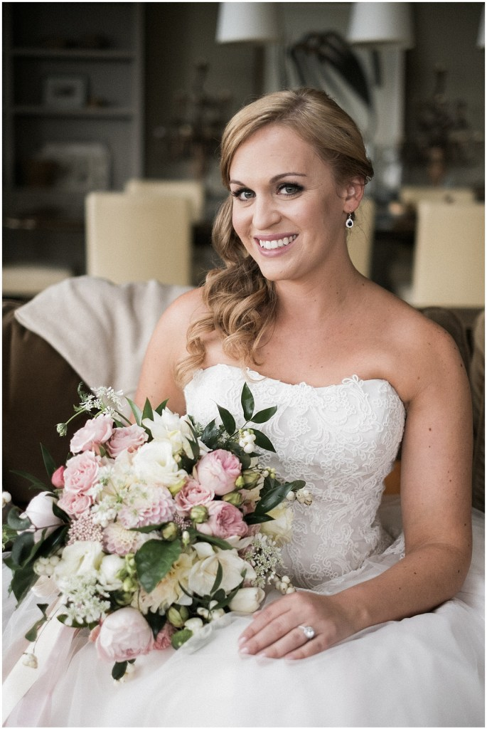 Bride in strapless gown poses inside while holding a large floral bouquet with ballerina pink and ivory colored flowers, The Foundry by Herban Feast wedding, fall wedding, Seattle wedding planner, Perfectly Posh Events, Photo by Lucas Mobley Photography