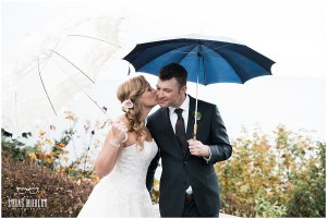 Bride and groom share a kiss outside on a rainy day while holding white and navy umbrellas, The Foundry by Herban Feast wedding, fall wedding, Seattle wedding planner, Perfectly Posh Events, Photo by Lucas Mobley Photography