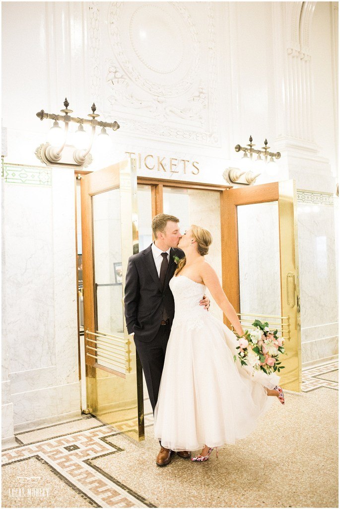Bride in a tea length wedding gown kisses her groom inside downtown Seattle's King Street Station, The Foundry by Herban Feast wedding, fall wedding, Seattle wedding planner, Perfectly Posh Events, Photo by Lucas Mobley Photography