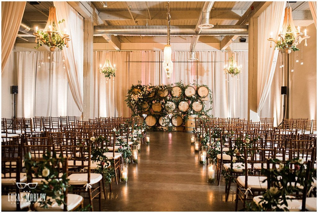 Indoor wedding ceremony set up with wood chairs draped with vines with a an altar made of wood wine barrels decorated with plenty of greenery and touches of ivory and pink florals, The Foundry by Herban Feast wedding, fall wedding, Seattle wedding planner, Perfectly Posh Events, Photo by Lucas Mobley Photography