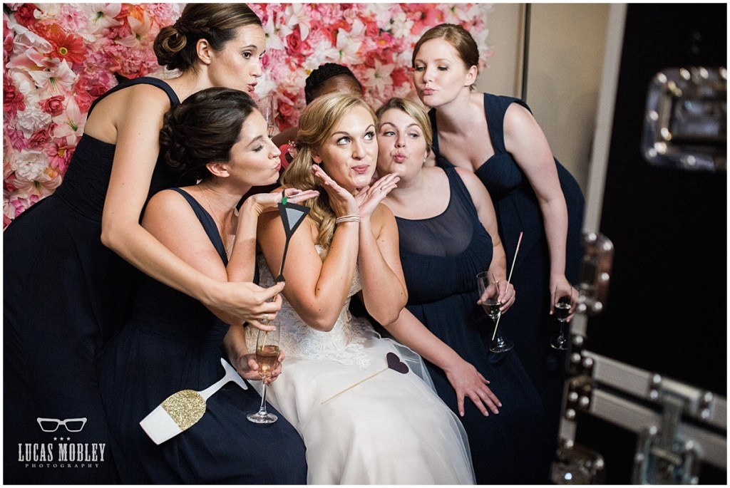 Bride poses with her bridesmaids with props for silly photos in a photo booth with a pink paper flower background, The Foundry by Herban Feast wedding, fall wedding, Seattle wedding planner, Perfectly Posh Events, Photo by Lucas Mobley Photography