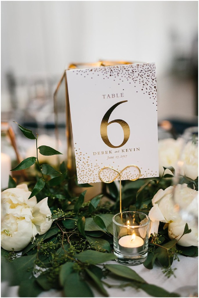 Custom made wedding table number surrounded with ivory flowers and greenery, same sex wedding, Sodo Park wedding, Seattle wedding coordinator, Perfectly Posh Events, Photo by Melissa Kilner Photography