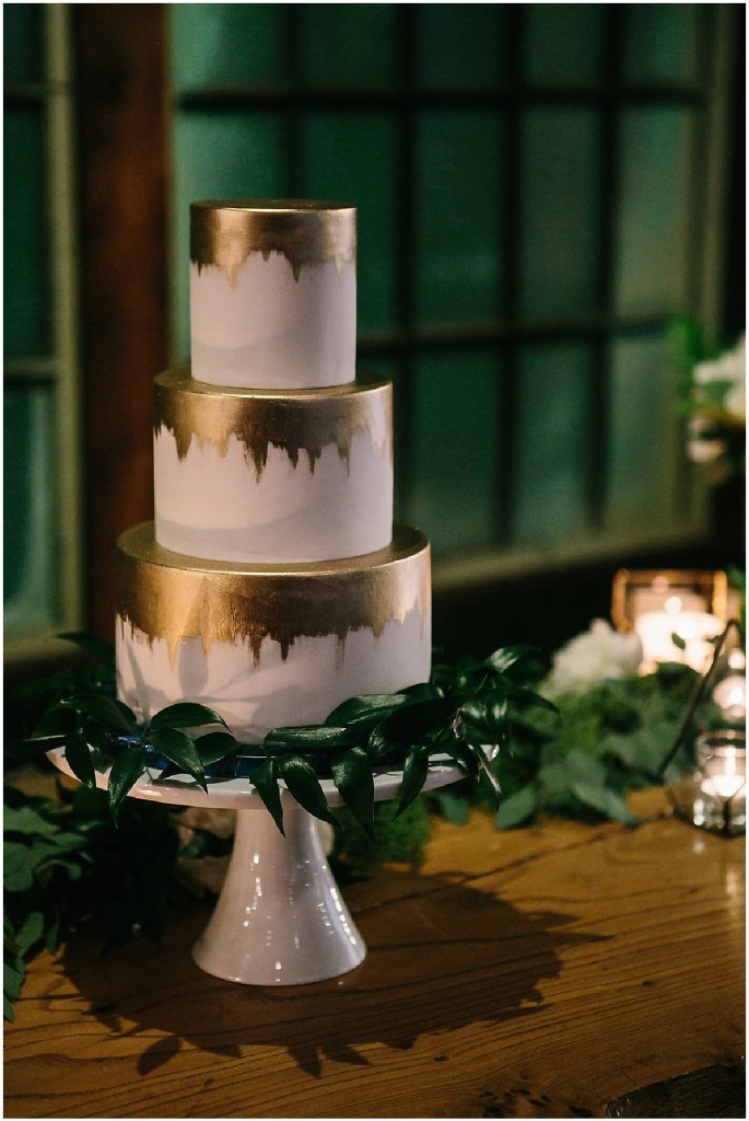 A three tier wedding cake covered in white and gold frosting sits on white cake stand surrounded with greenery, same sex wedding, Sodo Park wedding, Seattle wedding coordinator, Perfectly Posh Events, Photo by Melissa Kilner Photography