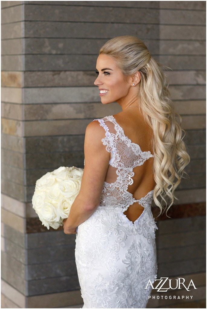 Back view of bride posing outside in a lace mermaid gown while holding a bridal bouquet made of white roses, Four Seasons wedding, Seattle wedding, Perfectly Posh Events event coordination, Photo by Azzura Photography