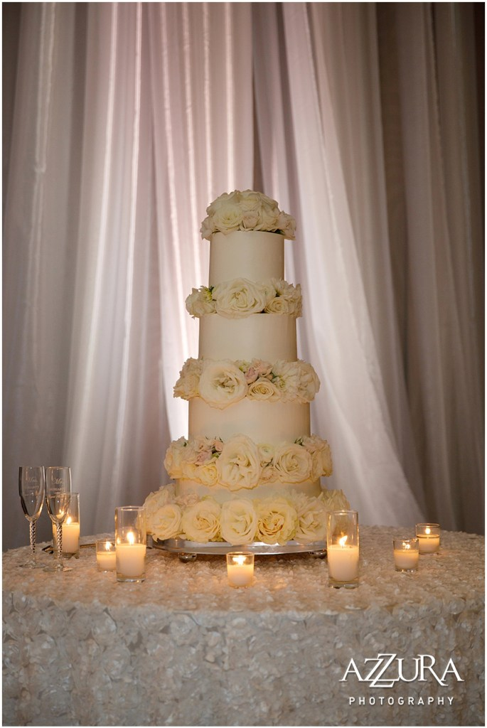 Four tier wedding cake covered in white frosting and decorated with white roses, Four Seasons wedding, Seattle wedding, Perfectly Posh Events event coordination, Photo by Azzura Photography