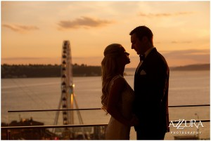 Bride and groom embrace each other at sunset with the Seattle Great Wheel in the background, Four Seasons wedding, Seattle wedding, Perfectly Posh Events event coordination, Photo by Azzura Photography