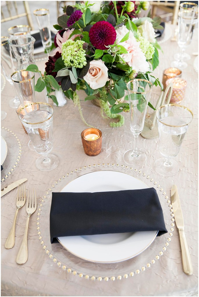 Wedding reception dinner place setting with white china, black napkins, and gold cutlery sitting on a champagne gold table cloth with a centerpiece made of blush pink and burgundy florals with touches of greenery, Laurel Creek Manor wedding, Perfectly Posh Events wedding coordination, Photo by Katie Parra Photography